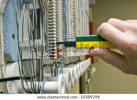 A man connecting wires on a punch block with a punch tool. - stock photo
