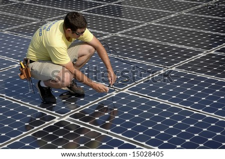 a man connects cables while installing a solar panel