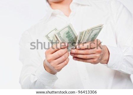 A man counting a handful of dollars. - stock photo