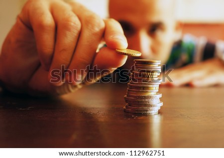 A man counts his coins on a table - stock photo