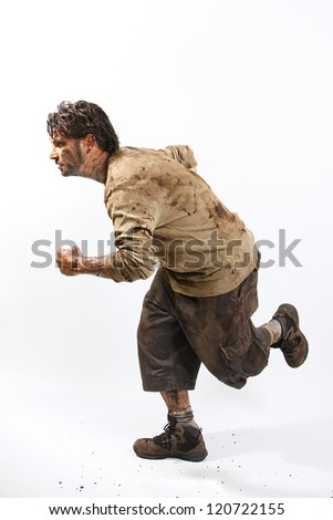A man covered in mud running, trying to survive