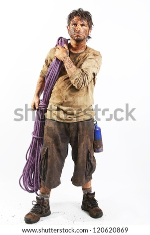 A man covered in mud with a rope, trying to survive