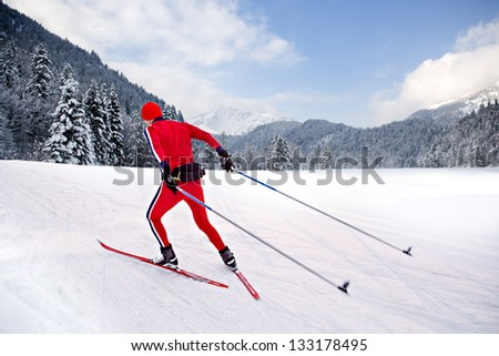 A man cross-country skiing in front of winter landscape - stock photo