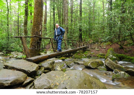 A man crosses a narrow footbridge over a rushing stream - stock photo