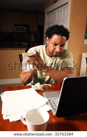 A man crumpling a piece of paper to start his work over