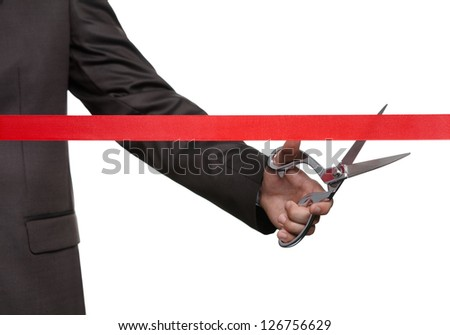 A man cutting a satin ribbon with scissors, isolated on white - stock photo