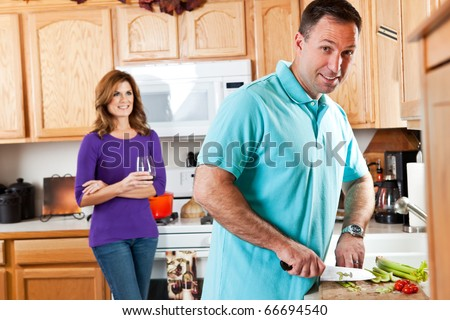 A man cutting vegetables preparing dinner with his wife watching in the background - stock photo