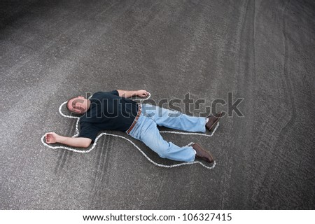 A man dead in the street outlined with chalk by crime scene investigators. - stock photo
