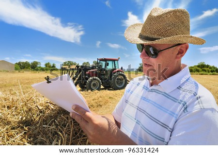 A man deals with paperwork, resting on a bale of hay, outdoors on a sunny day with blue skies. A tractor is seen in background. - stock photo