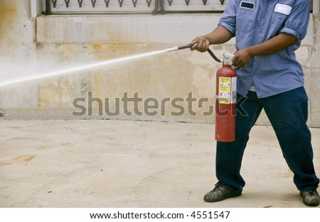A man demonstrating how to use a fire extinguisher during a fire safety practice session. - stock photo