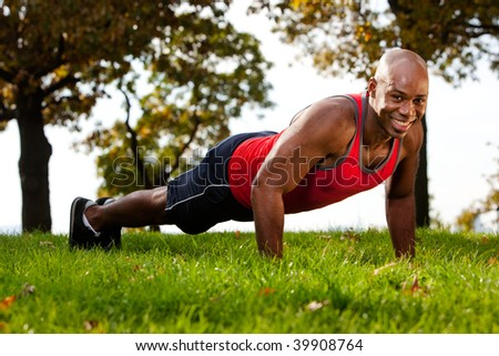 A man doing a push up in a park - stock photo