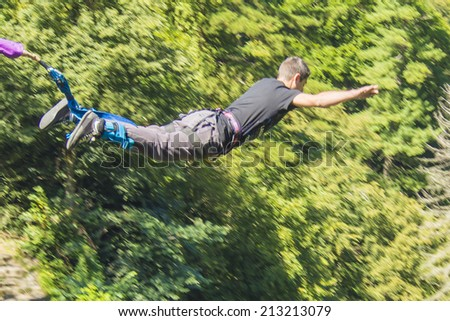 a man doing bungee jumping with a forest in background - stock photo