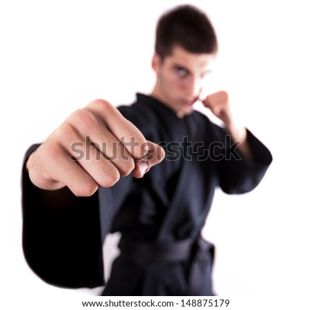 A man doing kickboxing and throwing a punch. Focus on the fist. - stock photo