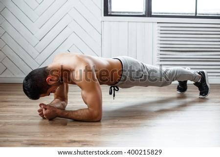 A man doing stomach workout on the floor. - stock photo