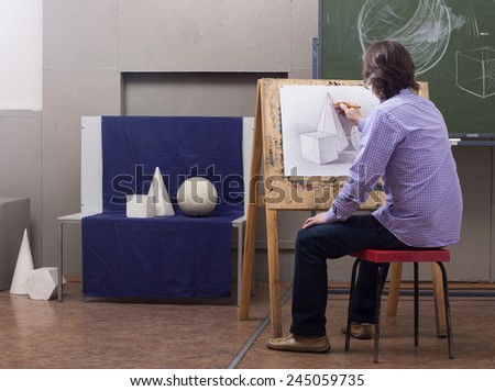 A man draws a pencil sitting at his easel. - stock photo