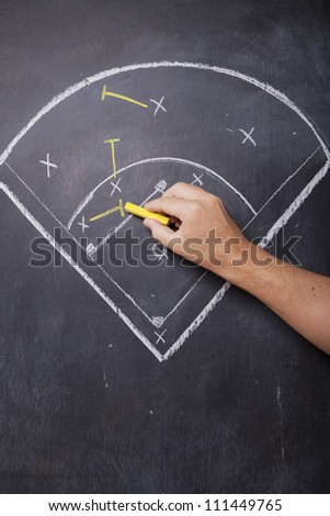 A man draws the positioning of a baseball team on a chalkboard. - stock photo