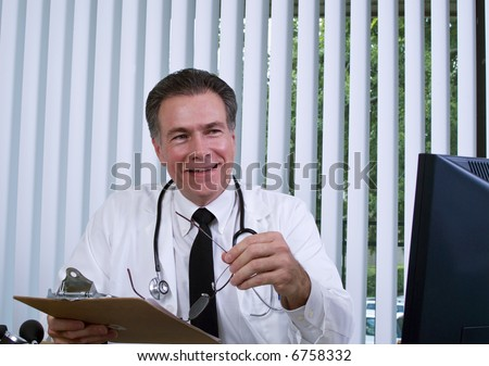 A man dressed as a doctor smiling and holding clipboard in his hand as if ready to give good news. - stock photo