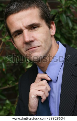 A man dressed in a suit has a hand on his tie. He looks like he's getting ready for some business. - stock photo
