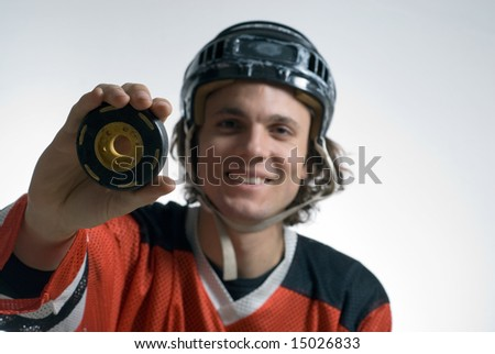 A man, dressed in an ice hockey uniform, smiles happily while holding a hockey puck. Horizontally framed shot. - stock photo