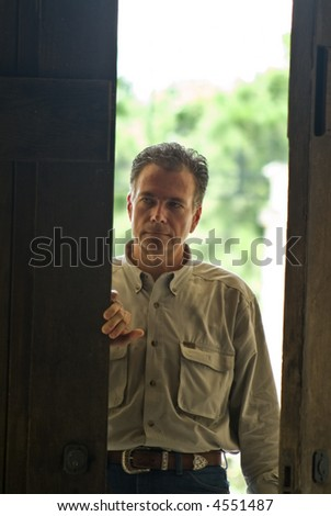 A man entering into a dark room with a sense of caution about him. - stock photo