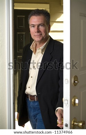 A man entering through his front door with a smile on his face. - stock photo