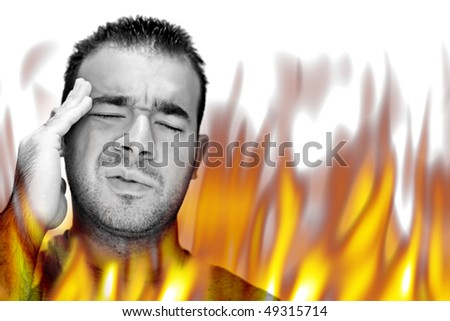 A man experiencing pain and suffering with hot fiery flames burning around him. - stock photo