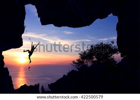 A man fall from climbing the cliff in front of the cave at sunset.