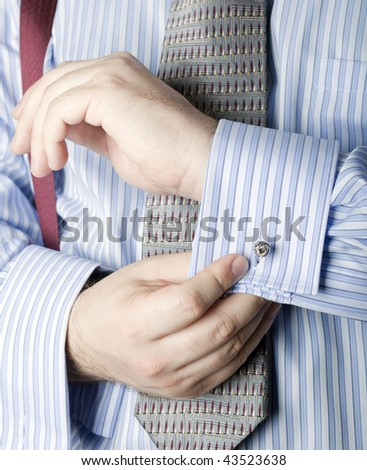 A man fastens the French cuffs of his shirt with a silver cufflink - stock photo