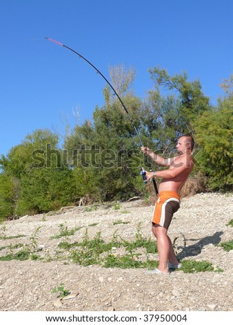 A man fighting with a catfish - stock photo