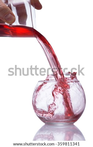A man fill a glass vessel  with red juice.  against a white background. The vessel reflects on the white table.Isolated on white.   - stock photo