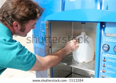 A man filling a water jug preparing for a hurricane.  Could also be used as example of recycling. (focus on hand and water bottle. ) - stock photo