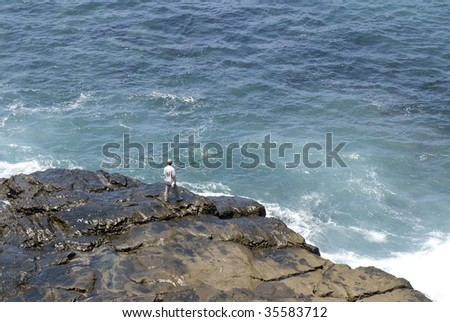 A man fishes on a remote reef, relaxing while engaging in his favorite outdoor hobby. - stock photo