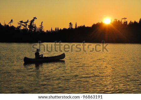 A Man Fishing From a Canoe at Sunset on a Remote Wilderness Lake - stock photo