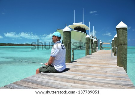 A man fishing from the wooden jetty. Exuma, Bahamas - stock photo