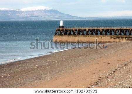 A man fishing off a sandy beach - stock photo