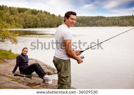 A man fishing on a lake with camping equipment and woman in background - stock photo