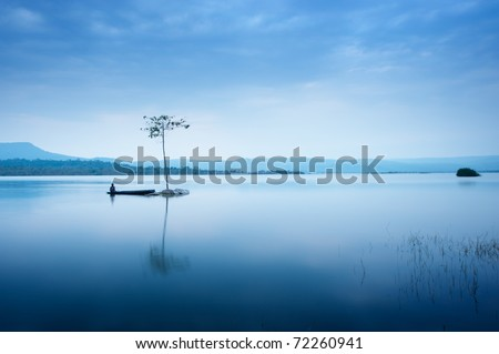 A man fishing on the boat near the tree. The blue water in the lake is very smooth . Reflection of everything in the water is clearly. Behind the river have big mountain. This time best for relaxing