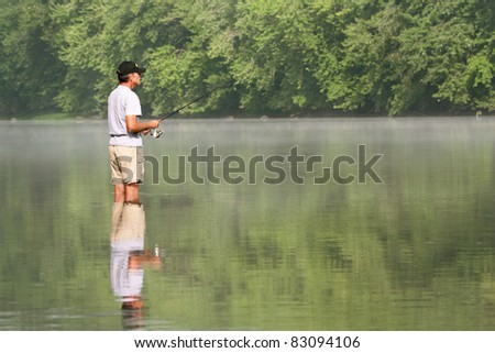 a man fishing while standing in the water with his reflection