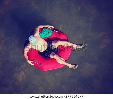 a man floating down a river in a blow up tube with a baseball cap on and shorts on a hot summer day from overhead toned with a retro vintage instagram filter effect - stock photo