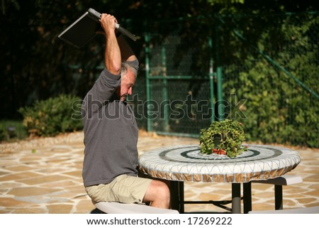A man frustrated with his lack of wireless connection and or computer skills takes his anger out by smashing his laptop to pieces - stock photo