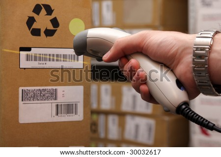 A man gets on the hip reader in operations directed on printed barcode. Warehouse scene. - stock photo