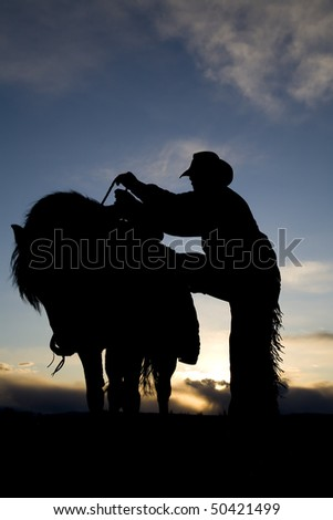 A man getting on his horse in the sunset - stock photo