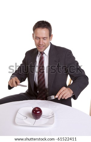A man getting ready to dig into an apple with his knife and fork. - stock photo