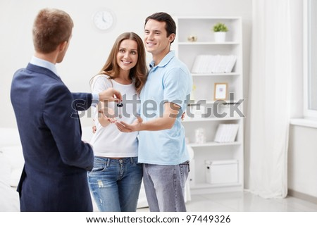 A man gives a couple of keys - stock photo