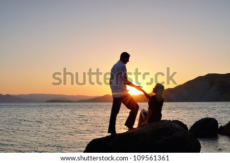 A man gives a woman's hand on the beach against the backdrop of the setting sun - stock photo