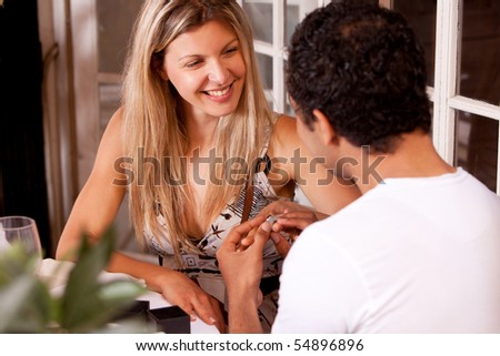 A man giving a ring as a gift to a female in an outdoor cafe - stock photo