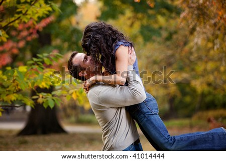 A man giving a woman a big hug in a park