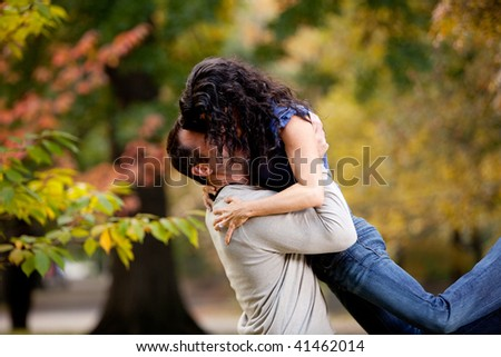 A man giving a woman a big hug in a park - stock photo