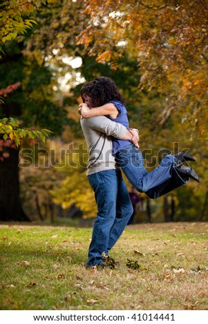 A man giving a woman a big hug - lifting her off the ground - stock photo