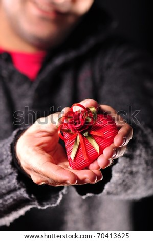 a man giving heart shaped gift - stock photo